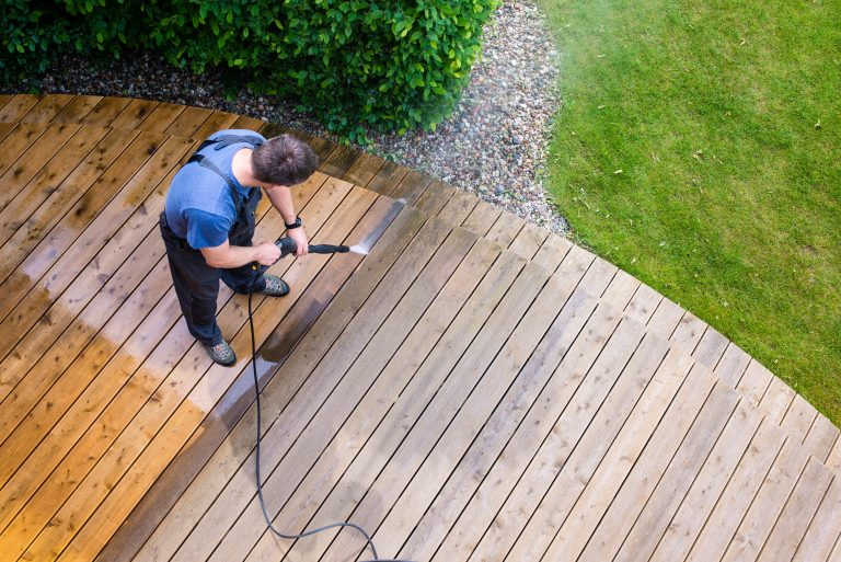 man pressure washing a deck with a electric pressure washer