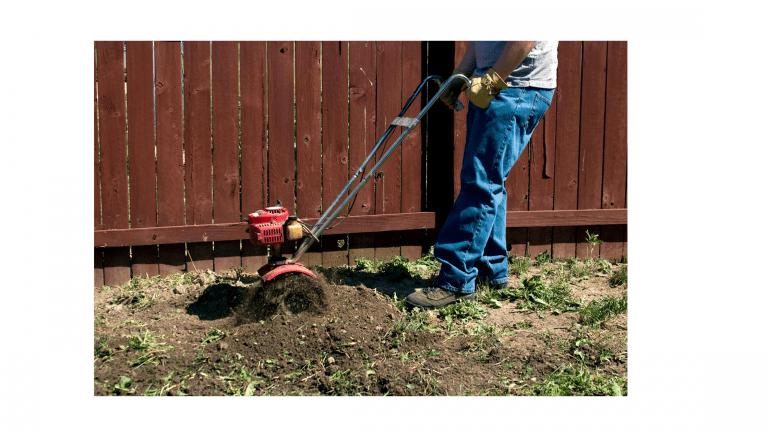 Man tilling garden with small tiller